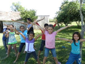 Kids' Club making the Letter X for the camera while they practice their alphabet.