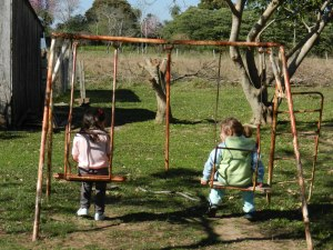 Girls swinging at the school playground, which is also my backyard. El Dia de Los Niños