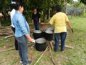 Señoras cooking lunch in large kettles over open fires for Fiesta Patronal