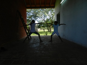Two sisters learning Warrior Pose.