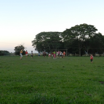 Evening girls' futbol practice. Kids and young boys play with girls until they are old/strong enough to play with the teens and young men.