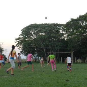 Colorful evening girls' futbol practice. Kids and young boys play with girls until they are old/strong enough to play with the teens and young men.