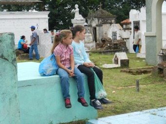 El Dia de los muertos (Day of the Dead) - a day-long fiesta of fun, food, and prayers to celebrate and remember loved ones who have passed. After friends have gathered for a short mass at a grave, the family of the deceased hands out candy. Here two girls by-pass the mass but attentively await the moment when the candy appears.